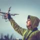 Drohnenversicherung: Ein Mann mit grüner Kapuzenjacke hält seine versicherte Drohne in der Hand.