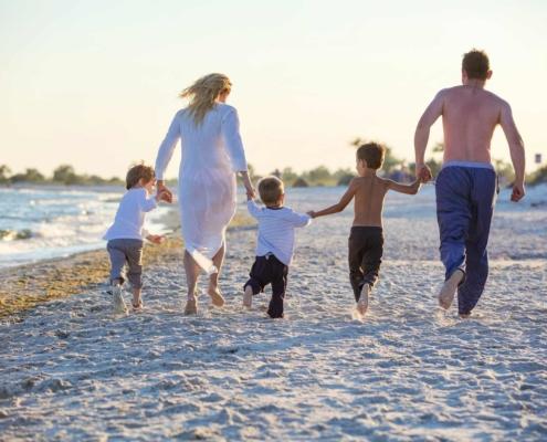3A Gebundene Vorsorge: Familie mit drei Kindern spazieren am Strand.