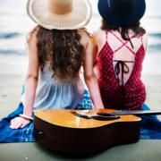 Musikinstrumente und Sportsachen Versicherung: Zwei junge Frauen sitzen am Strand mit dem Rücken zur Kamera und im Vordergrund liegt eine Gitarre auf dem Sand.