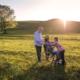 Rente bei Krankheit und Unfall: Großeltern und Enkel auf der Weide am spazieren. Das junge Mädchen hält die Oma auf dem Rollstuhl an den Schultern fest und lächelt Sie an.