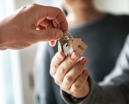 Mietkaution: Hausschlüsselübergabe an eine glückliche junge Familie dank der Mietkaution Versicherung.