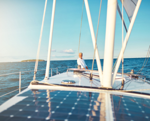 Bootsversicherung: Ein glücklicher Mann auf seinem Boot, er hat eine Bootsversicherung abgeschlossen und segelt nun auf dem offenen Meer. Im Hintergrund ist auch eine Insel zu sehen.