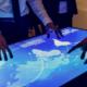 Cyber Risk und IT Versicherung: Digitaler Tisch mit der Weltkarte und Männern drumrum, die sich über Schutzmöglichkeit vor Cyber Attacken beraten.