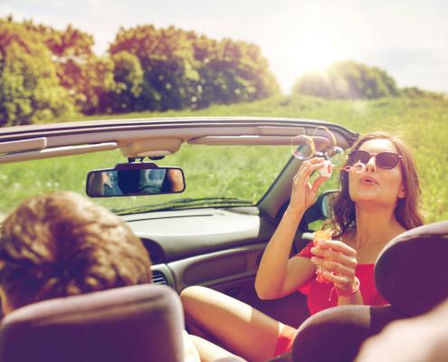 Fahrzeugversicherung: Mann fährt Auto. Eine Fahrzeugversicherung wurde abgeschlossen. Frau mit Sonnenbrille sitzt daneben und pustet Seifenblasen nach hinten zur Kamera.