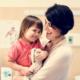 Krankenkasse: Glückliche Mutter mit ihrer Tochter auf dem Arm. Mit der Krankenkassen Versicherung sind sie bei Behandlungen in sicheren Händen.
