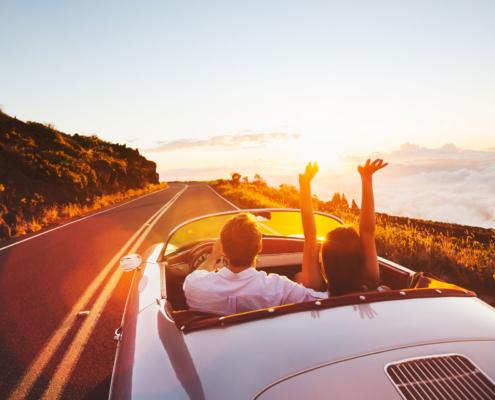 Oldtimerversicherung: Ein junges Paar fahren in einem Oldtimer durch eine Küstenstraße beim Sonnenuntergang.