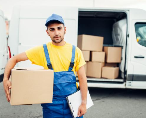 Transportversicherung: Ein Lieferant mit einem Paket unter dem Arm und dem Transporter im Hintergrund. Eine Transportversicherung wird für Transporte aller Art benötigt.